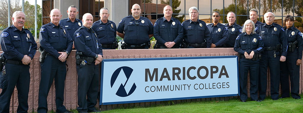 Photo of MCCCD Police Officers standing in front of an MCCCD sign at District Office